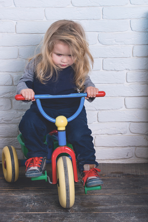 Boy riding bicycle in room. Child and tricycle. Baby cyclist with long blond hair on white brick wall. Playing and having fun. Happy childhood concept. Stock Photo