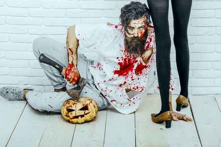 Halloween female legs standing in black pantyhose and shoes. Man sitting with pumpkin and axe on wooden floor. Bearded hipster with red blood splatters. Halloween holiday celebration concept Stock Photo