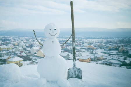 Christmas or xmas decoration. Happy holiday and celebration. New year snowman from white snow outdoor. Winter activity and party. Snowman with shovel.
