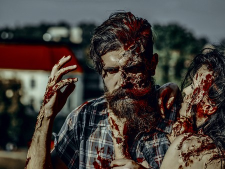 Halloween horror and violence. Woman strangling man with bloody hands. Girl with bloody brunette hair. Vampire with beard and red blood wounds outdoors. Holiday celebration concept.