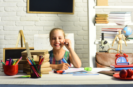 Girl laughs and does homework. Childhood and back to school concept. Kid with colorful stationery on white wall background. Pupil with books and school supplies. Stok Fotoğraf