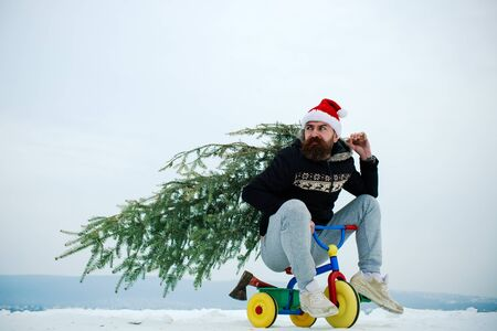 Cyclist in santa hat and sporty wear on winter day. Christmas and new year. Holiday celebration concept. Man riding tricycle on snowy landscape. Hipster carrying xmas tree on white snow.