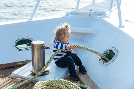 Boy kid playing with rope on yacht. Little child sitting and berthing rope on white boat. Travel and summer vacations. Baby care and childhood. Yachting and sailing concept.
