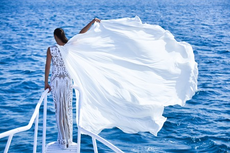 Girl in white wedding dress, back view. Honeymoon travel concept. Bride on sunny windy day on blue water. Summer vacation and holidays. Woman posing on ship bridge.
