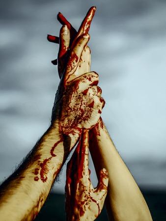 회색 하늘 배경에 할로윈 피 묻은 손입니다. 뱀파이어 손을 스트레칭 붉은 혈액. 미치광이 또는 살인자 개념. 할로윈 휴가 축하