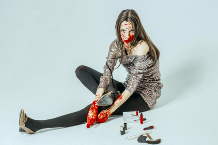 Halloween woman sitting on floor isolated on white. Girl with bloody face and hands. Fashion model in grey party dress with makeup kit. Halloween make up concept.