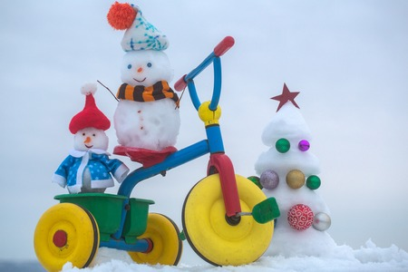 Snowmen riding tricycle on snowy background. Snow sculptures and xmas tree on grey sky. Christmas and new year celebration. Winter holidays concept.