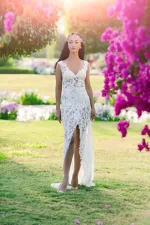 Vrouw in witte kleding en tiara in lang donkerbruin haar die zich op groen gras in tuin met tot bloei komende bomen op zonnige dag op natuurlijke achtergrond bevinden. Schoonheidskoningin concept. Huwelijksreis en zomervakantie Stockfoto
