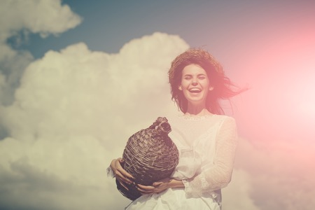 Happy woman in white dress and wreath on brunette hair. Summer vacation, holidays and celebration. Harvesting and winemaking. Winery tour concept. Girl smiling with wicker wine bottle on cloudy sky.