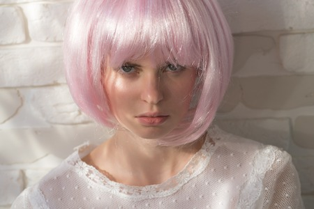 Beauty and cosmetics. Girl posing in pink wig. Model with cute face on white brick wall. Woman with light beams on skin. Health and skincare concept.