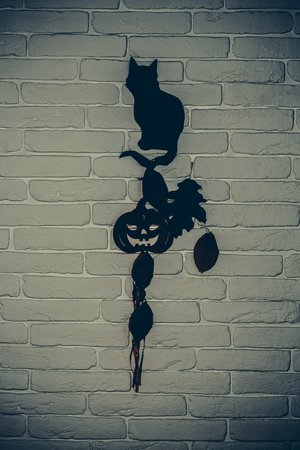 Halloween black cat, pumpkin and tree leaves silhouette paper cutouts on grey brick wall. Mystery and superstition concept. Holiday celebration symbols Фото со стока