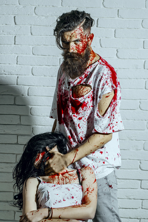 Halloween man putting bloody hand on woman neck. Bearded hipster and girl on white brick wall. Maniac and victim with red blood splatters. Horror and violence. Halloween holiday concept
