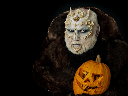 Man with orange pumpkin. Monster with dragon skin and grey beard on face. Demon in fur coat on black background. Alien or reptilian makeup with sharp thorns and warts. Horror and halloween concept.