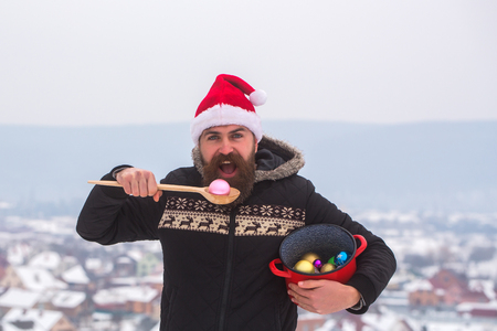 Hipster with wooden spoon and pot. Christmas and new year celebration. Guy with open mouth in red santa claus hat and coat. Winter holidays concept. Santa man eating xmas balls on snowy landscape.