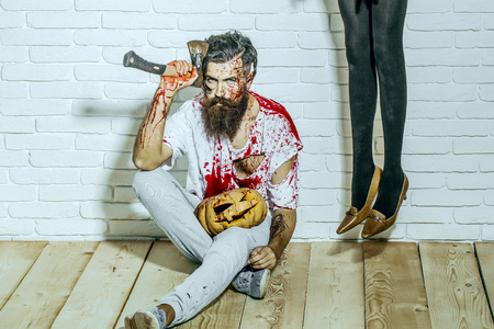 Halloween bearded hipster with red blood. Female legs in black pantyhose hanging on white wall. Man sitting with bloody pumpkin and axe on wooden floor. Crime and violence. Halloween holiday concept Stock Photo