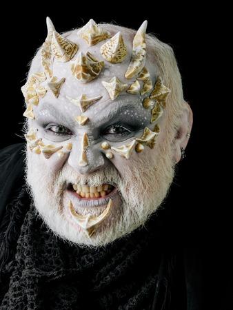흰 눈과 검은 색 바탕에 수염 난된 얼굴을 가진 이빨을 가시 화가 괴물 남자. 공포와 판타지 개념입니다.