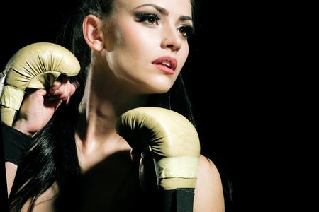 코치와 건강. 검은 색 바탕에 섹시 한 여자 권투 선수의 운동입니다. 힘과 에너지. 스포츠와 성공. 권투 장갑 및 운동복 여자입니다.