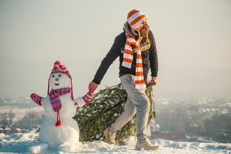 Mens en sneeuwman die op blauwe hemel lopen. Hipster slepende Kerstmis boom op besneeuwde winter weg. Kerstmis en Nieuwjaar. Kerel en sneeuwbeeld die hoeden en sjaals dragen. Vakantie feest concept.