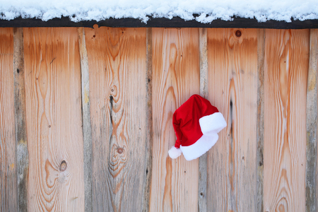 Santa claus hat on snowy fence. Red santa cap on wooden background. Winter palisade with white snow. Christmas and new year. Holidays celebration concept. Stock Photo