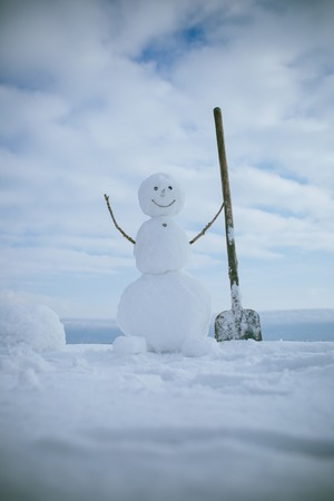 New year snowman from white snow outdoor. Christmas or xmas decoration. Winter activity and party. Happy holiday and celebration. Snowman with shovel.