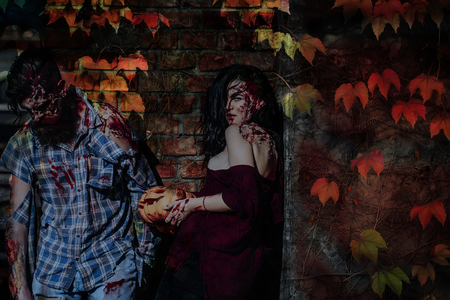 Halloween couple standing on brick wall with autumn leaves. Zombie man and woman with wounds and red blood. Girl holding bloody pumpkin. Halloween holiday celebration concept Stock Photo
