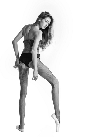 woman ballerina with long hair and legs in pointe shoes and leather body suit, black and white Stock Photo