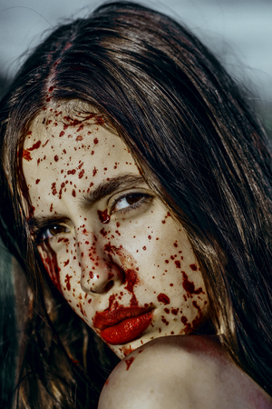 Halloween woman with blood splatters on face. Girl with bloody red lips. Vampire with long brunette hair. Halloween holiday celebration concept.