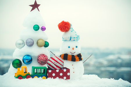 Snow sculptures on white sky background. Snowman with smiley face in hat and scarf. Christmas tree with decorations, toy train and present box. xmas and new year. Winter holidays concept. Stock Photo