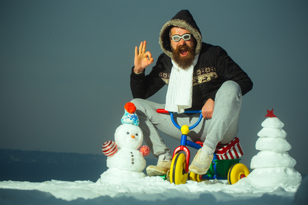 Happy man riding tricycle on grey sky. Hipster in pilot glasses and hood showing ok gesture. Christmas and new year fun. Snowman and snow xmas tree on winter landscape. Holiday celebration concept.