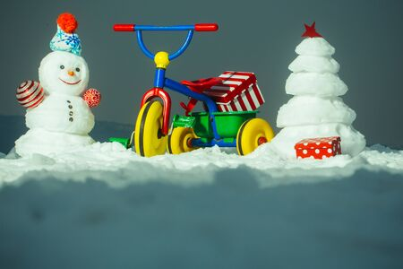 Tricycle with present box on snowy background. Snowman and snow xmas tree on grey sky. Christmas and new year celebration. Festive surprise and gifts. Winter holidays concept Stock Photo