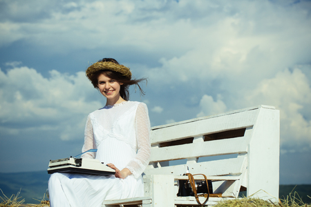 Happy girl in wreath and white dress on bench. Assistant or secretary working on nature on sunny day. Summer vacation concept. Vintage equipment and archaism. Woman typing on typewriter on cloudy sky.