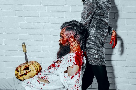 Halloween man sitting with pumpkin stabbed with knife. Bearded hipster with red blood splatters on white brick wall. Female maniac in silver dress with bloody hands. Halloween holiday concept Stock Photo
