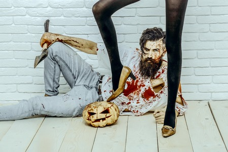 Halloween hipster sitting with pumpkin and axe on wooden floor. Female legs black pantyhose and shoes standing on pumpkin. Bearded man with red blood splatters. Halloween holiday celebration concept Stock Photo