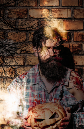 Halloween hipster holding pumpkin with ghostly light beams. Bearded man with wounds and red blood. Zombie in bloody torn shirt. Bare branches of dead trees on brick wall. Halloween holiday concept.
