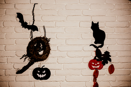 Halloween holiday celebration symbols. Black and red pumpkins, cat, bat, tree leaves and nest silhouette paper cutouts on beige brick wall. Mystery and superstition concept.