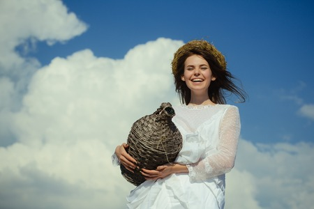 Happy girl smiling with wicker wine bottle on cloudy sky. Harvesting and winemaking. Winery tour concept. Summer vacation, holidays and celebration. Woman in white dress and wreath on brunette hair. Фото со стока