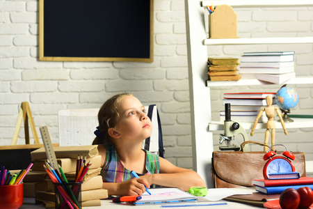 Childhood and back to school concept. Girl with thoughtful face expression does homework. Pupil with books and school supplies. Kid with colorful stationery on white wall background.