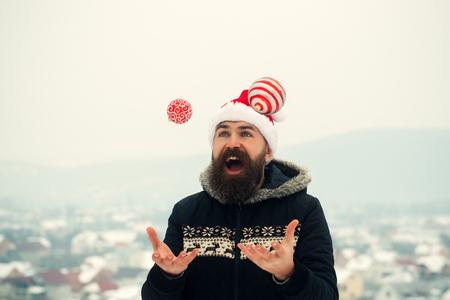 雪景色のクリスマス ボールをジャグリング サンタ男。幸せなヒップスター喜びで口を開きます。サンタ クロースの赤い帽子とコートの男。クリス