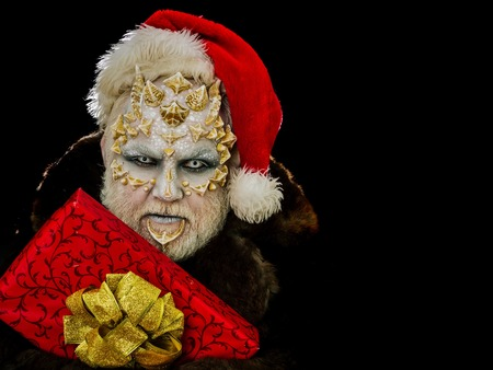 New year and christmas concept. Monster in santa hat and fur coat. Man with red present box. Elf with dragon skin and beard. Sorcerer face with white eyes and sharp thorns, copy space