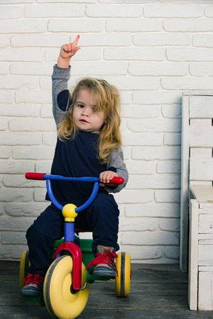 Happy childhood concept. Baby cyclist with long blond hair on white brick wall. Boy riding bicycle in room. Playing and having fun. Child rising index finger on tricycle.