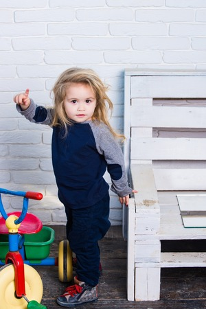 Boy in children room with toys. Toddler pointing index finger up. Child with long blond hair on white brick wall. Playing and having fun. Happy childhood concept.