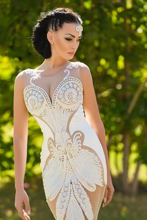 Bruid in witte sexy kleding op zonnige dag. Vrouw met juwelentiara in donkerbruin haar. Meisje poseren op onscherpe natuurlijke achtergrond. Schoonheidskoningin concept. Huwelijksreis en zomervakantie