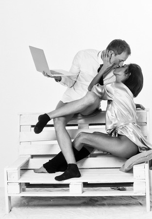 young kissing couple of handsome man or businessman and pretty woman or girl working on portable laptop or computer in shirt, socks and tie, sits on wooden bench at home isolated on white background