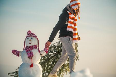 Kerel en sneeuwbeeld die hoeden en sjaals dragen. Kerstmis en Nieuwjaar. Vakantie feest concept. Mens en sneeuwman die op blauwe hemel lopen. Hipster slepende Kerstmis boom op besneeuwde winter weg. Stockfoto - 86246889