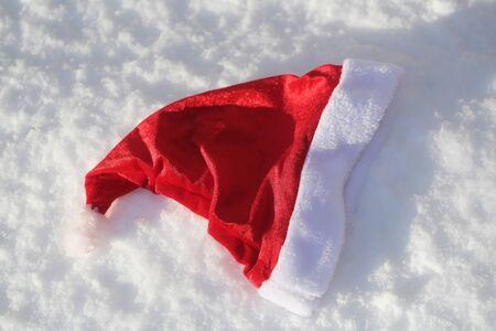 눈 덮인 배경에 산타 클로스 모자입니다. 눈에 산타 빨간 모자입니다. 크리스마스와 새 해입니다. 겨울 흰 풍경입니다. 크리스마스 휴일 축 하 개념입 스톡 콘텐츠