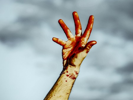 Halloween bloody fingers on grey sky background. Male hand bleeding with red blood. Vampire or zombie hand. Halloween holiday celebration concept. Stock Photo