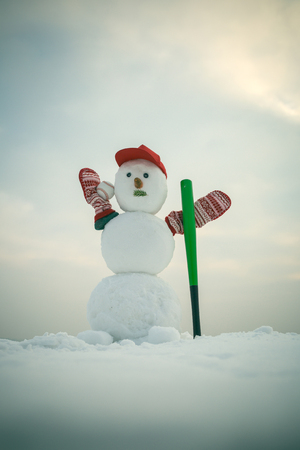 Winter activity, sport and fighting. New year snowman from snow in cap and mittens. Snowman with baseball bat. Happy holiday and celebration. Christmas or xmas decoration.