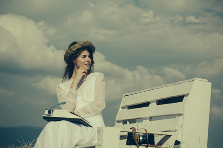 Assistant or secretary working on nature on sunny day. Vintage equipment and archaism. Summer vacation concept. Woman typing on typewriter on cloudy sky. Girl in wreath and white dress on bench.