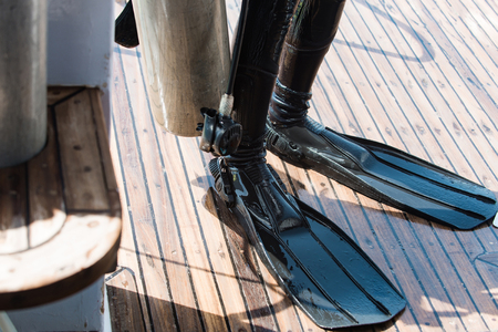 Legs in black rubber wetsuit and flippers on wooden deck equipment for scuba diving on summer vacations and travel Stock Photo - 85976205