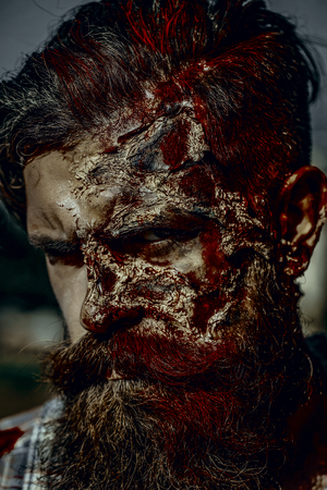 Halloween man with bloody beard and hair. War soldier with wounds on face. Zombie on sunny day outdoors. Vampire hipster with red blood. Holiday celebration concept.
